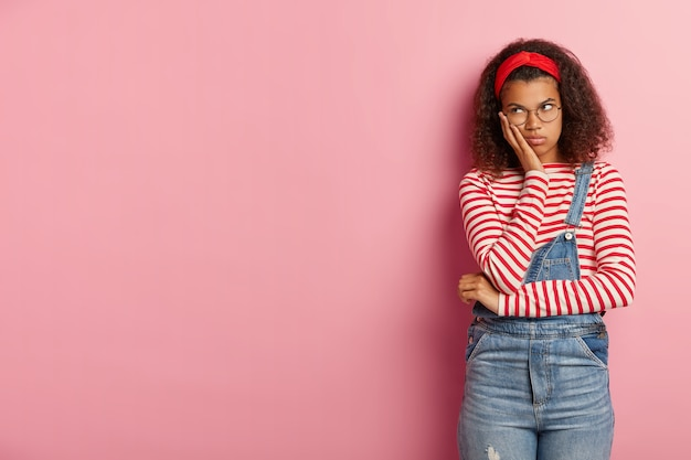Shot of gloomy unhappy teenage girl posing in overalls with curly hair