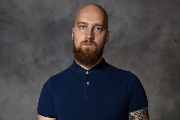 Shot of gloomy young bald male with bushy beard being dissatisfied with unfair results of competition, pursuing lips, trying to hide his anger,