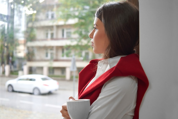 Shot of a gorgeous young woman relaxing standing by the window looking away thoughtdully holding cup of coffee copyspace people living lifestyle morning dreaming concept.