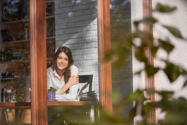 Shot of a gorgeous young woman sitting near the window at the local cafe looking out smiling happily copyspace positivity happiness emotions expressive beauty relaxation lifestyle leisure urban.