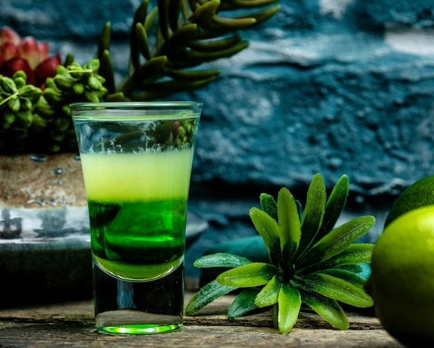 Shot of green cocktail with herbs