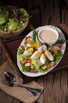 Shot of green salad with radish and hard-boiled egg on white plate with fork and napkin