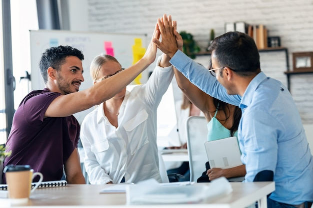 Shot of group of successful smart business team celebrating good job while holding up their right hands on coworking place.