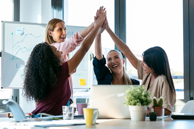 Shot of group of successful smart business women holding up their right hands on coworking place.