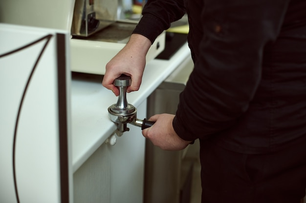 Shot of hand of barista holding coffee tamper and making coffee preparation