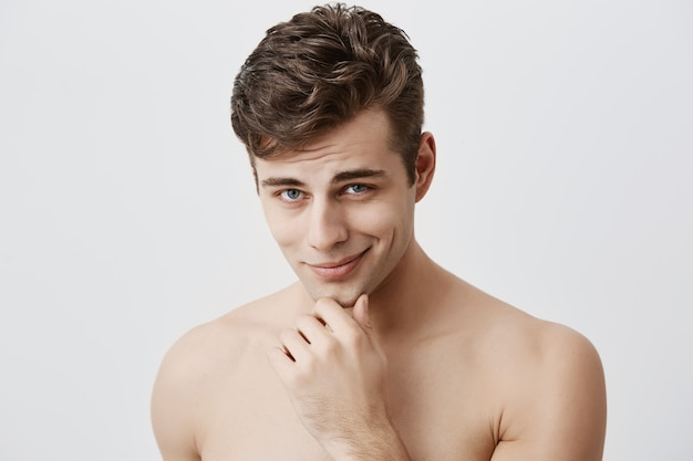 Shot of handsome attractive young caucasian male expressing positive emotions as has good mood after walk with girlfriend. pleasant looking guy smiles  holding hand under his chin.