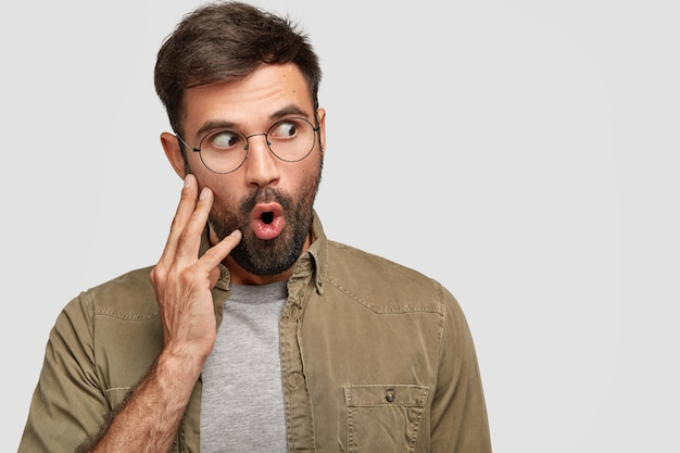 Shot of handsome unshaven male has bristle, looks with suprirsed expression aside, keeps lips rounded, notices something interesting, isolated on white wall