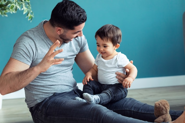Shot of handsome young father with his baby playing together and having fun at home.