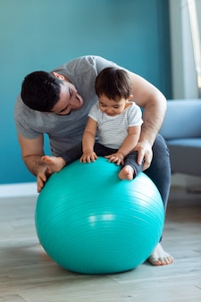 Shot of handsome young father with his baby playing together and having fun with the ball at home.