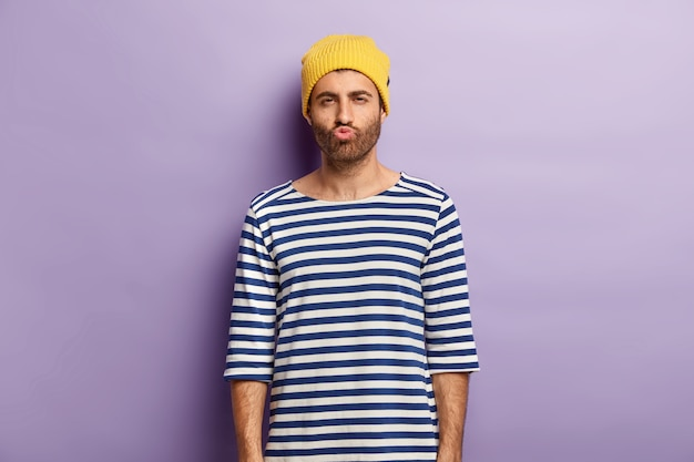 Shot of handsome youngster with bristle pouts lips and looks mysteriously, being dissatisfied with something, wears yellow hat and striped sailor jumper