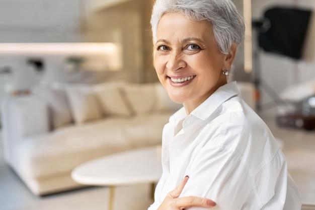 Colpo di felice cinquantenne donna in pensione con lentiggini e capelli grigi in posa su interni eleganti sfondo, indossa una camicia bianca, sorridente largamente davanti