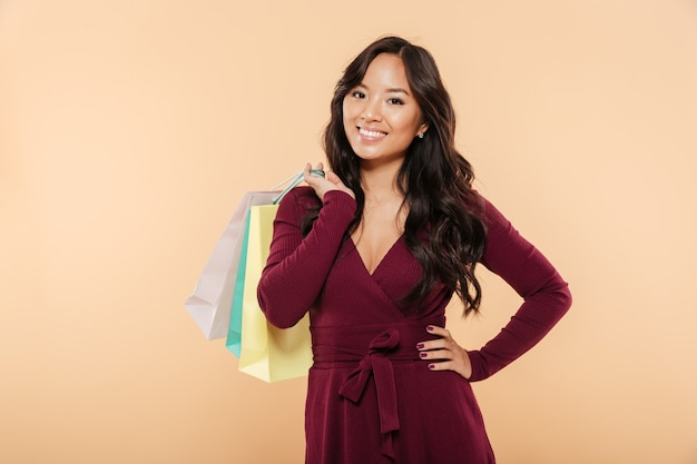 Shot of happy asian lady in maroon dress posing over beige background holding packs with purchases after shopping on sale day