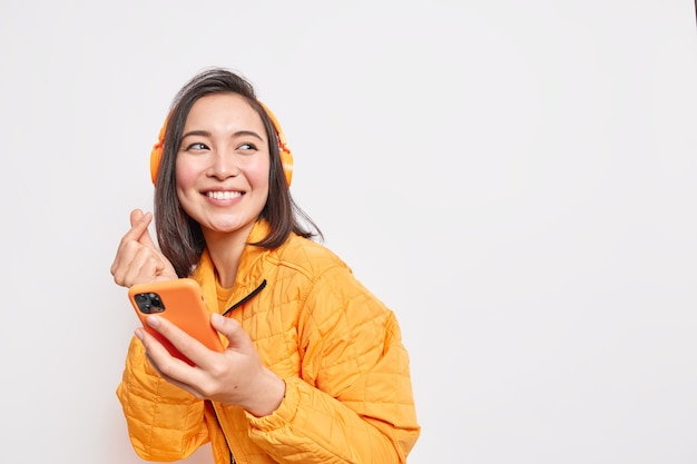 Shot of happy asian millennial girl makes eastern like sign smiles gladfully looks away dressed in orange jacket uses smartphone and headphones for listening favorite music poses indoor