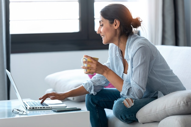 Shot of happy business woman working remotely from home with laptop and drinking coffee while sitting on sofa.