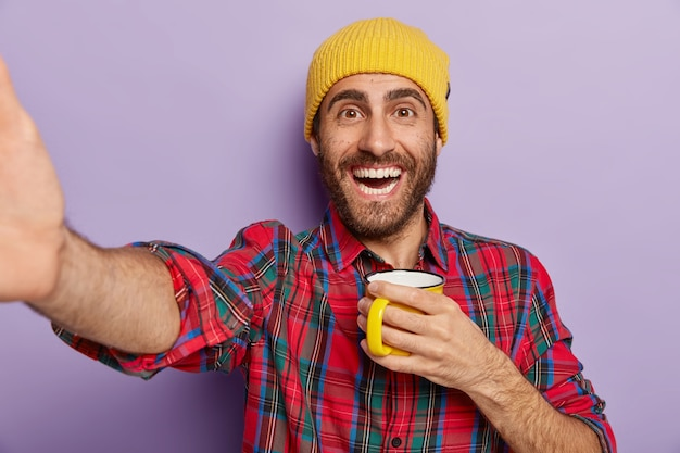 Shot of happy caucasian man takes selfie indoor, holds mug with coffee or tea, enjoys break and free time, wears stylish yellow hat and plaid shirt isolated on purple wall. people and lifestyle