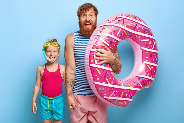 Shot of happy ginger father and daughter posing in pool outfits
