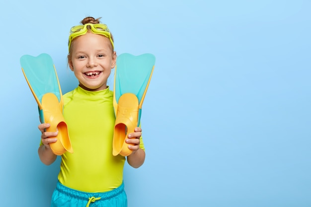 Shot of happy ginger small girl shows new rubber flippers, wears swim goggles, dressed in summer clothes, enjoys learning swimming, has active rest, isolated on blue wall with blank space