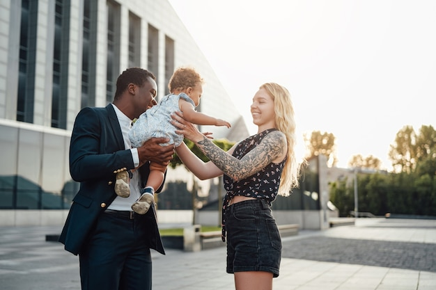 Shot of happy mixed family of father giving his daughter to his wife outside.