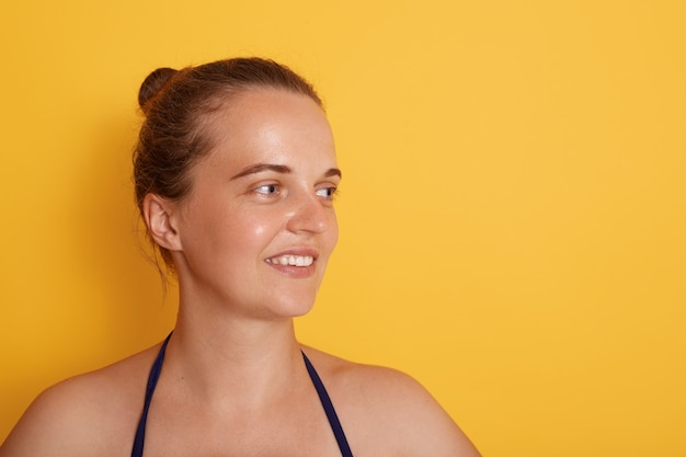Shot of happy young caucasian woman with tender smile, looks aside with charming expression, wears swimming suit, has natural beauty, isolated over yellow wall.