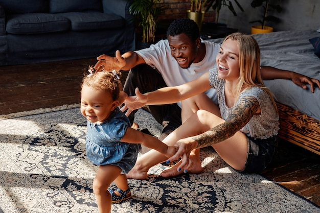 Shot of happy young family of multiracial couple with their child playing in bedroom.