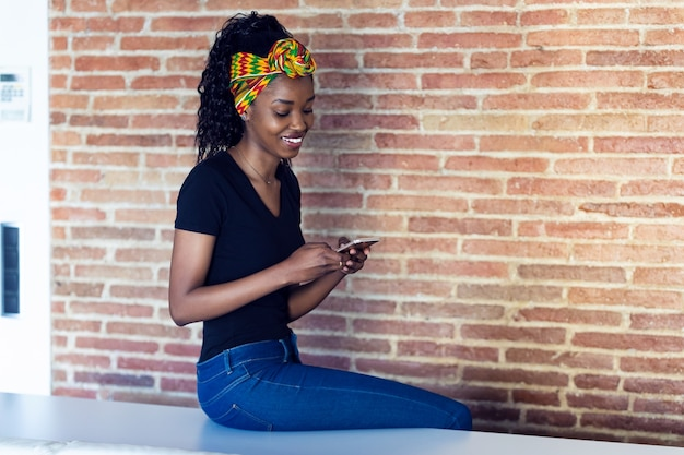 Shot of happy young woman talking on mobile phone while sitting on a table in front of a wall.