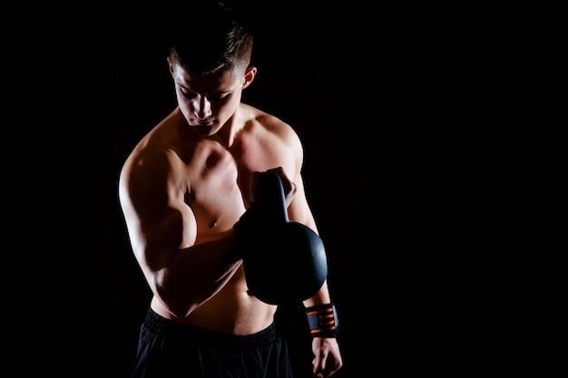 Shot of healthy muscular young man doing weight exercise with dumbbells