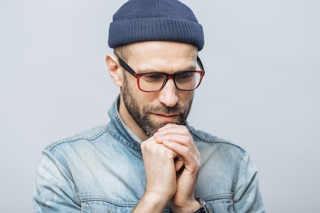 Shot of hopeful bearded male looks with thoughtful expression down, keeps hands together
