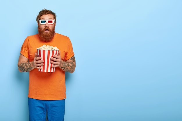 Shot of impressed bearded redhead man eats popcorn