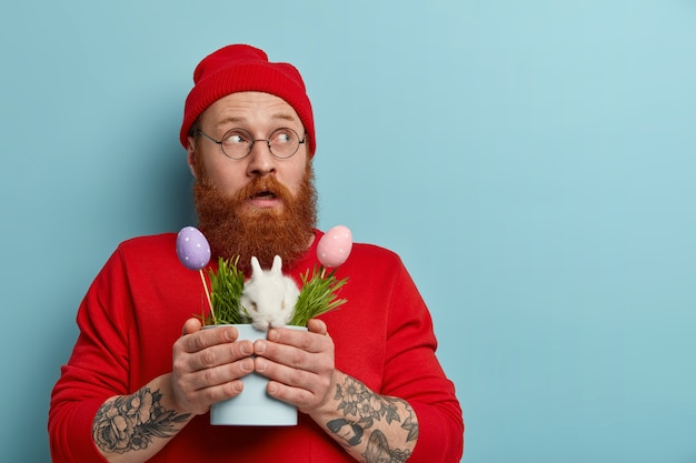 Shot of impressed pensive guy turns gaze aside, holds symbols of spring and easter, prepares for egg hunt, carries white bunny in pot, has puzzled reaction, wears red hat and sweater.