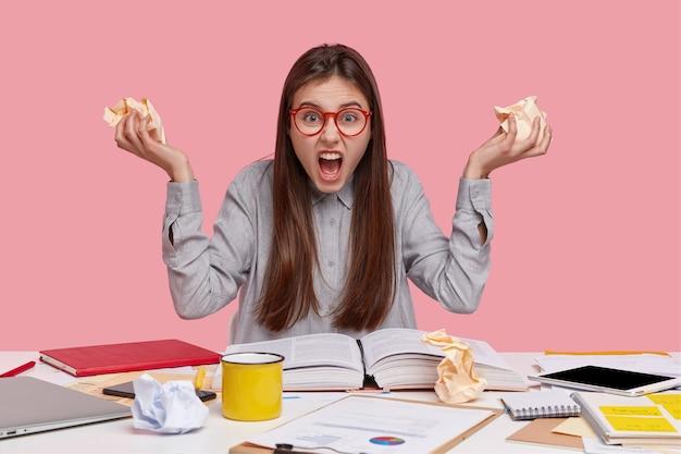 Inquadratura di un giovane operaio irritato tiene in mano una rupe di carta, grida con espressione depressa, ha molto lavoro, legge libri