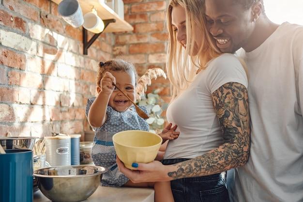 Shot of joyful multiethnic family enjoying their vacations together on cozy kitchen.