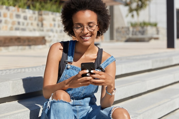 Shot of joyful teenager with dark skin, curly hair, reads comments on her blog, watches video online in social networks, wears casual denim dungarees, poses at stairs alone, connected to 3g.
