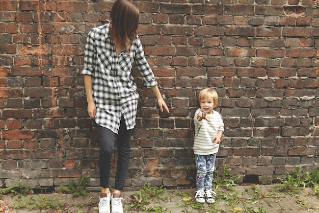 Shot of little boy with his caring sister near brick wall. skinny caucasian girl dressed in checked shirt, black trousers. she stretching arm to younger brother, but he pulling his hand ahead.