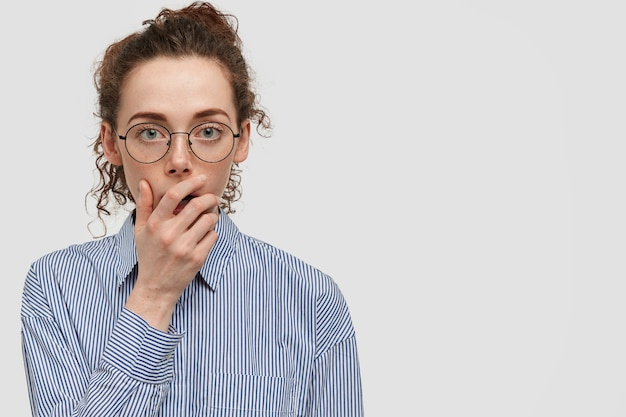 Shot of lovely attentive serious european female keeps hand on mouth, listens necessary information with great interest, wears round spectacles, poses against white wall with blank space