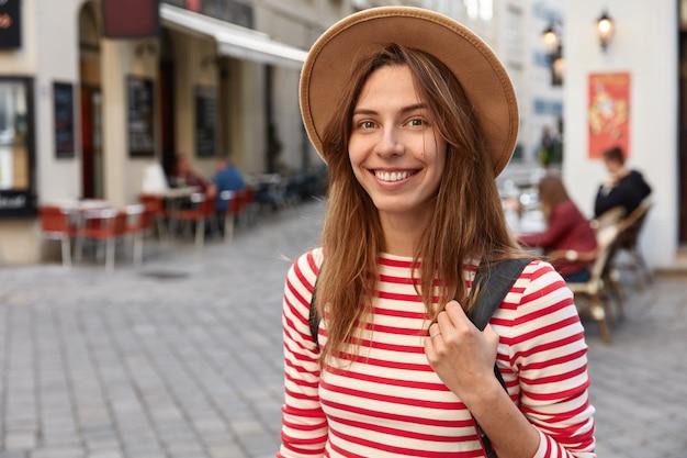 Colpo di bella donna sorride volentieri, indossa cappello e maglione a righe, essendo di buon umore mentre passeggia per la città