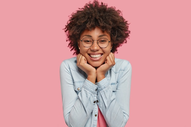 Shot of lovely happy dark skinned female has afro hairstyle, smiles broadly, shows white perfect teeth, glad to recieve compliment, dressed in denim jacket, isolated over pink wall