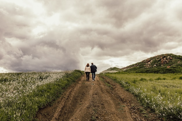 Shot of a male and female walking along a pathway in a valley with flowers under a foggy sky