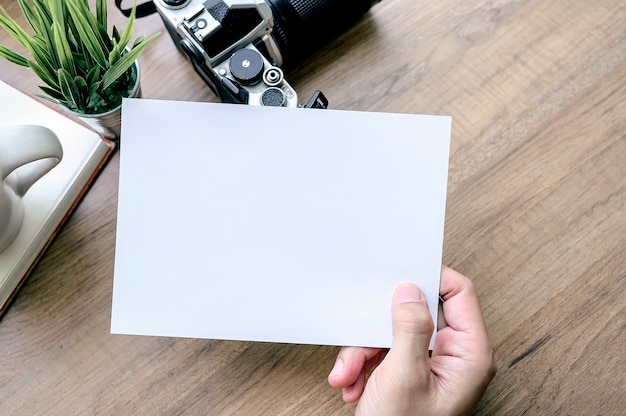 Shot of man hand holding white card with camera on wooden table. top view.