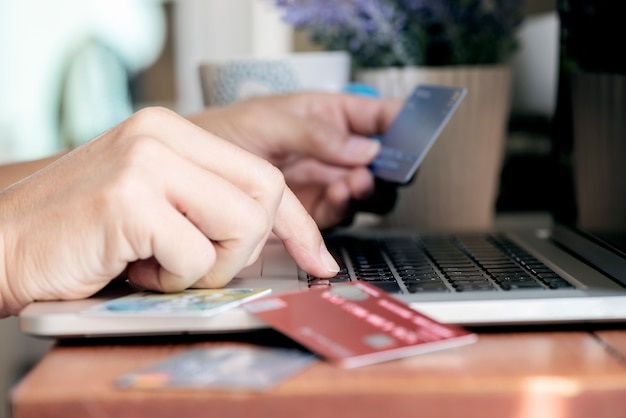 Shot of man hand typing on laptop and holding credit card, online transactions concept.