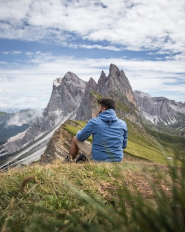 Shot of a man looking at the valley and mountains of puez-geisler nature park, italy