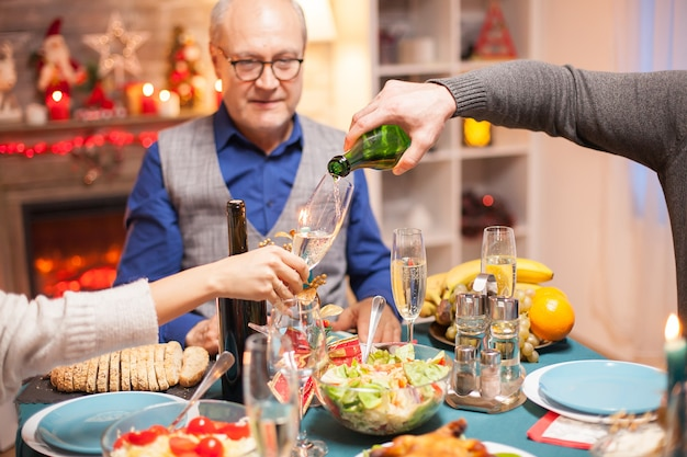 Shot of man pouring wine in a glass at christmas family dinner.