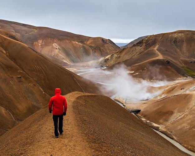 Dietro il tiro di un uomo con un cappotto rosso che cammina attraverso le colline della regione delle highlands, islanda