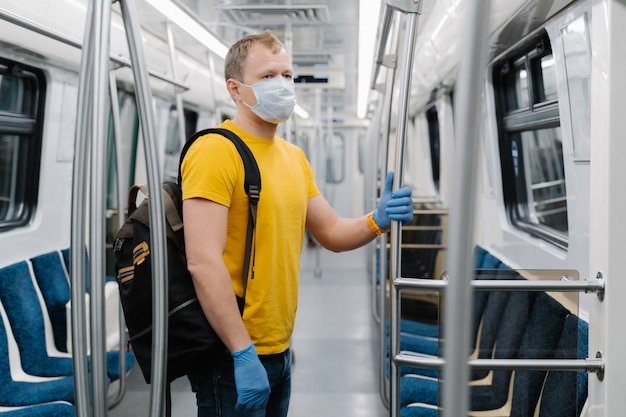 Shot of man wears disposable medical mask during coronavirus outbreak, keeps safety, poses in empty carriage