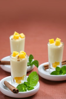 Shot mango sorbet with cinnamon, dessert for catering of a celebration.