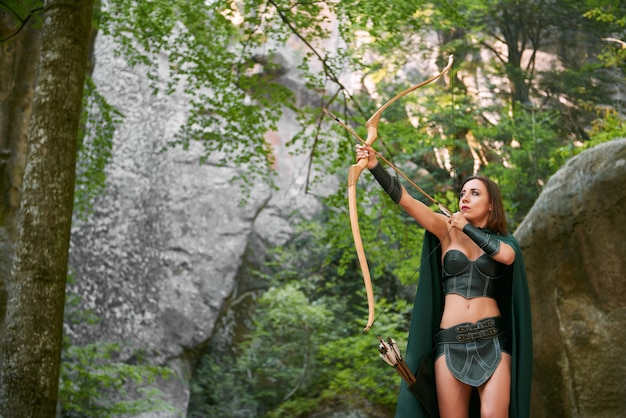 Shot of a mature female amazon archer hunting in the woods with bow and arrows copyspace nature outdoors hunter tribe tribal traditional history character cosplay costume.