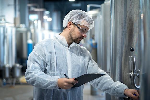 Colpo del lavoratore tecnologo concentrato di mezza età che controlla la produzione nell'industria chimica o farmaceutica