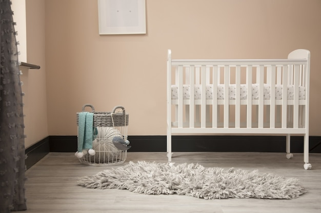 Shot of minimalistic sunny baby's room interior with child's bed.