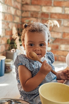 Shot of mixed race little girl holding wooden spoon on table on cozy kitchen in daytime.