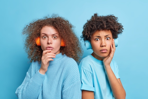 Shot of mixed race two women stand shocked stare speechless pose back to eath other have curly hair wear stereo headphones listen music isolated over blue wall. friendship concept