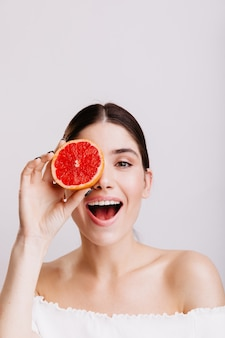 Shot of model with gray eyes on isolated wall. positive girl without makeup covers eye with half grapefruit.